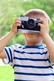 Ragazzo allegro felice con una macchina fotografica, il bambino fotografato all'aperto immagini stock libere da diritti