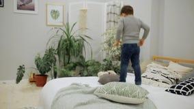 Ragazzo 5-7 anni in blue jeans e un aspetto europeo del maglione grigio che salta felicemente sul letto nei genitori archivi video