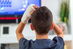 Ragazzo anonimo con il braccio rotto che guarda TV fotografia stock libera da diritti