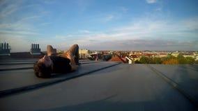 Ragazzo ansante che si siede sul tetto che trascura la città stock footage