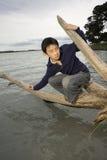 Ragazzo asiatico che equilibra sul libro macchina sopra acqua immagini stock