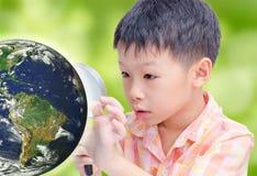 Ragazzo asiatico che esamina globo d'ardore dalla lente d'ingrandimento Fotografia Stock