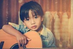 Ragazzo asiatico che gioca chitarra acustica Immagini Stock Libere da Diritti