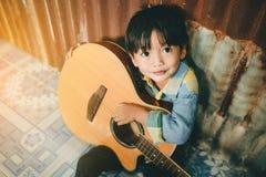 Ragazzo asiatico che gioca chitarra acustica Fotografie Stock Libere da Diritti
