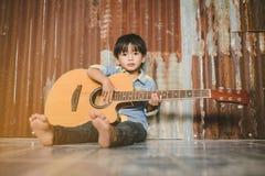 Ragazzo asiatico che gioca chitarra acustica Fotografia Stock Libera da Diritti
