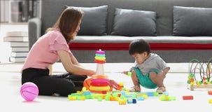 Ragazzo asiatico che gioca i blocchetti del mattone con sua madre archivi video
