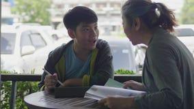 Ragazzo asiatico che gioca il computer della compressa e che parla con sua madre, fronte di sorriso video d archivio
