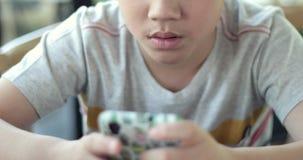 Ragazzo asiatico che gioca sullo Smart Phone stock footage