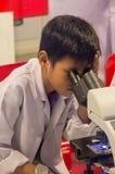 Ragazzo asiatico che guarda tramite il microscopio Immagini Stock Libere da Diritti