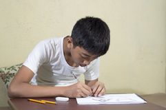 Ragazzo asiatico che impara e che pratica disegnare le forme 3D sul taccuino del disegno sullo scrittorio marrone a casa Fotografia Stock