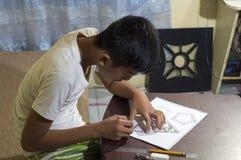 Ragazzo asiatico che impara e che pratica disegnare le forme 3D sul taccuino del disegno sullo scrittorio marrone a casa Immagine Stock