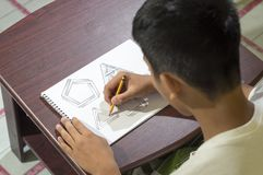 Ragazzo asiatico che impara e che pratica disegnare le forme 3D sul taccuino del disegno sullo scrittorio marrone a casa Fotografia Stock Libera da Diritti