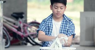 Ragazzo asiatico che lava a mano il suo asciugamano, piccolo ragazzo facente tailandese di lavoro domestico a casa archivi video