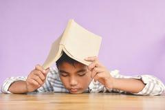 Ragazzo asiatico che legge un libro Fotografia Stock
