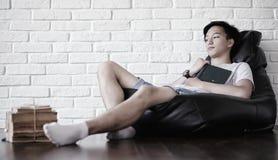 Ragazzo asiatico che legge un libro e una caduta addormentati Immagine Stock Libera da Diritti