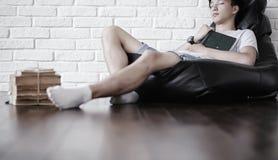 Ragazzo asiatico che legge un libro e una caduta addormentati Immagini Stock Libere da Diritti