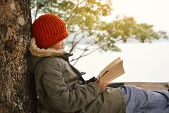 Ragazzo asiatico che legge un libro sul parco Immagine Stock Libera da Diritti