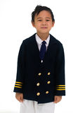 Ragazzo asiatico che porta un'uniforme surdimensionata del pilota, sorridente felicemente I fotografie stock libere da diritti