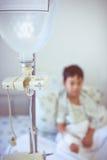 Ragazzo asiatico che si siede sul letto di ammalato con il dispositivo di venipunzione IV d della pompa per infusione Fotografia Stock Libera da Diritti