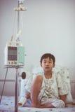 Ragazzo asiatico che si siede sul letto di ammalato con il dispositivo di venipunzione IV d della pompa per infusione Fotografia Stock