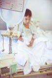 Ragazzo asiatico che si siede sul letto di ammalato con il dispositivo di venipunzione IV d della pompa per infusione Immagini Stock Libere da Diritti