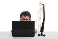 Ragazzo asiatico che studia con il computer portatile Immagine Stock