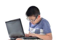 Ragazzo asiatico con il computer portatile che si siede sul bianco Fotografia Stock