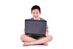 Ragazzo asiatico con il computer portatile che si siede sul fondo bianco Fotografie Stock