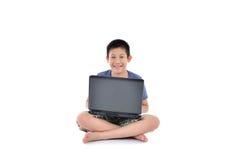 Ragazzo asiatico con il computer portatile che si siede sul fondo bianco Immagine Stock Libera da Diritti