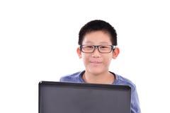 Ragazzo asiatico con il computer portatile che si siede sul fondo bianco Fotografia Stock Libera da Diritti