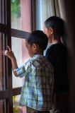 Ragazzo asiatico due vicino alle finestre Immagini Stock Libere da Diritti