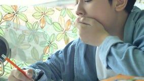 Ragazzo asiatico felice che fa il vostro compito con il fronte di sorriso 4K video d archivio