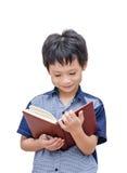Ragazzo asiatico felice che legge un libro Fotografia Stock