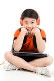 Ragazzo asiatico felice che per mezzo del computer portatile Fotografia Stock Libera da Diritti