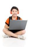 Ragazzo asiatico felice che per mezzo del computer portatile Fotografia Stock