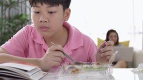 ragazzo asiatico 4K che mangia pranzo a casa, stock footage