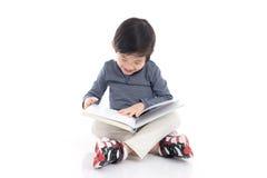 Ragazzo asiatico sveglio che legge un libro Immagini Stock