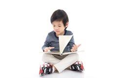 Ragazzo asiatico sveglio che legge un libro Fotografia Stock