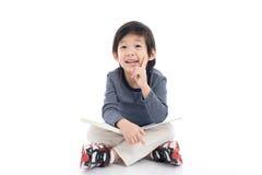 Ragazzo asiatico sveglio che legge un libro Immagine Stock Libera da Diritti