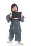 Ragazzo asiatico sveglio che tiene bordo nero su fondo bianco Fotografie Stock Libere da Diritti