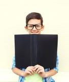 Ragazzo astuto sorridente dell'adolescente del ritratto in vetri con la cartella o il libro Immagini Stock Libere da Diritti