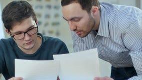 Ragazzo attento che studia con un computer portatile mentre insegnante che lo aiuta archivi video