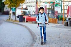 Ragazzo attivo del bambino della scuola nella guida del casco di sicurezza con il suo motorino nella città con lo zaino il giorno immagini stock
