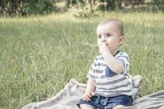 Ragazzo bady sveglio con i grandi bei occhi che si siedono sull'erba all'aperto sulla natura Fotografia Stock Libera da Diritti