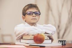 Ragazzo, bambino, alla scuola, ad uno scrittorio della scuola con i libri Fotografia Stock Libera da Diritti