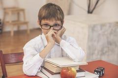 Ragazzo, bambino, alla scuola, ad uno scrittorio della scuola con i libri Immagini Stock