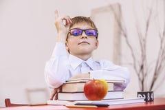 Ragazzo, bambino, alla scuola, ad uno scrittorio della scuola con i libri nel glasse Fotografia Stock Libera da Diritti
