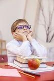 Ragazzo, bambino, alla scuola, ad uno scrittorio della scuola con i libri nel glasse Fotografie Stock Libere da Diritti