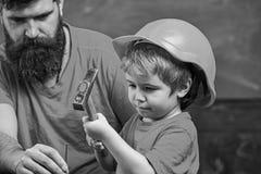 Ragazzo, bambino occupato in casco protettivo imparante utilizzare martello con il papà Concetto di paternità Padre con insegname immagine stock libera da diritti