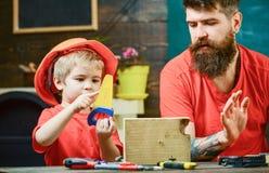 Ragazzo, bambino occupato in casco protettivo imparante utilizzare sega a mano con il papà Concetto educativo dei giochi Padre, g fotografia stock libera da diritti